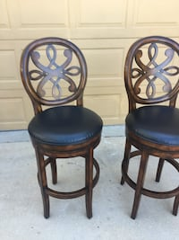 two black leather padded brown wooden chairs Bradenton, 34203