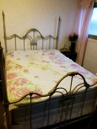 brown wooden bed frame with white and pink floral bedspread Vaughan