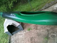 green and black seat-in kayak and white-and-black doghouse