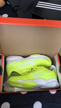 pair of green Nike running shoes with box