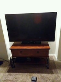 black flat screen TV with brown wooden TV stand Hobart, 46342