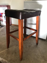 2 brown wooden barstools with brown leather padded seat