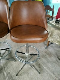 two brown leather padded bar stools