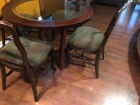 """Kitchen dining table with 4 chairs. Chair cushions are a little rough. It's used and all wood with round glass insert. Measures 42"""" in diameter and 30"""" in height. Price is firm, no delivery  1377 mi"""