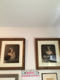two brown wooden framed paintings