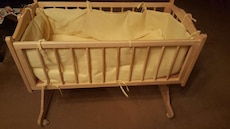 baby's white wooden cradle with white crib bumpers