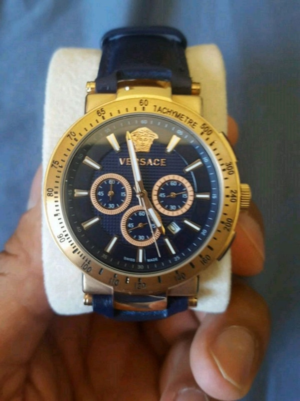 round gold-colored chronograph watch with blue str