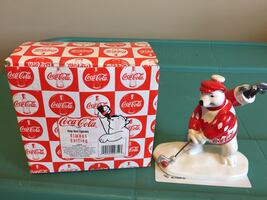 Bear wearing red suit figurine with white and red coca-cola box