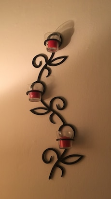 Decorative metal wall sconce with candles