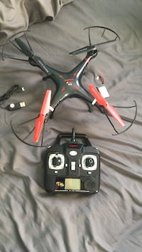 black and red quadcopter with controller