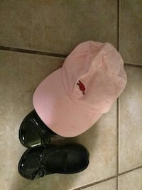 A pair of baby black shoes and a baby girls hat.