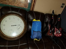 round brown wooden frame chronograph clock; blue bag; two red gaming guitar controllers