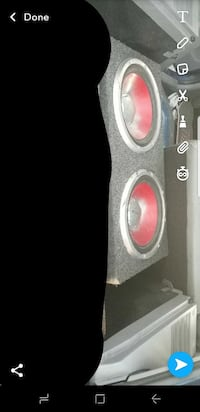 two round red subwoofers with black enclosure