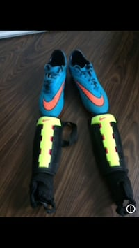 pair of blue-and-orange Nike cleats and shin guards