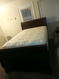 Full sized mattress with sleigh bedframe as well a
