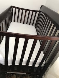 Baby's brown wooden crib with mattress it has some scratches
