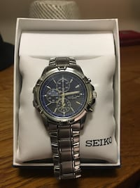 Seiko chronograph watch with silver link bracelet and blue background