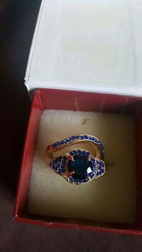 silver-colored ring with blue gemstone and box