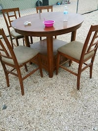 round brown wooden table with four chairs dining set North Las Vegas, 89030