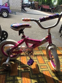 girl's pink Barbie bicycle with training wheels