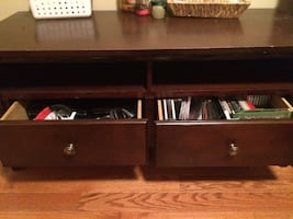 Wooden tv stand with storage areas.