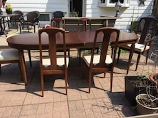 Oval brown wooden dining table with chairs