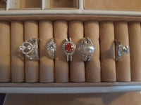 six assorted silver-colored cluster rings