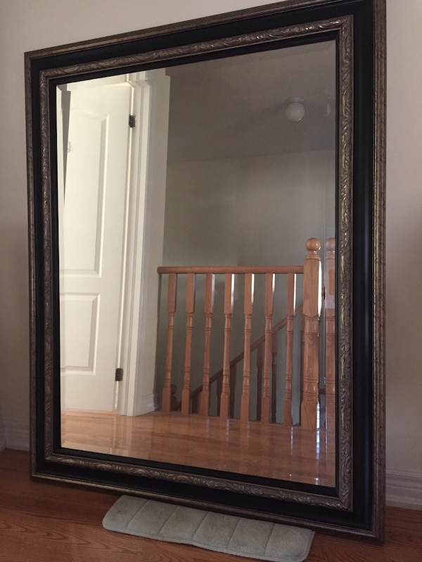 Rectangular black and brown wooden framed leaning mirror