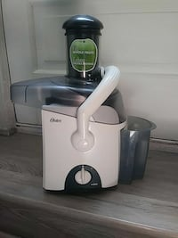 Oster juicer with cup. 38 mi