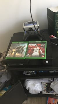 Black xbox one console with controller and game cases