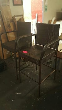 two black wicker bar stools