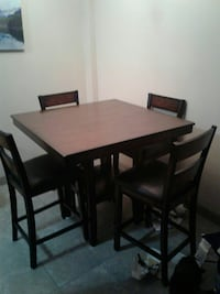 square brown wooden table with four padded chairs dining set Calgary, T2V 0H6