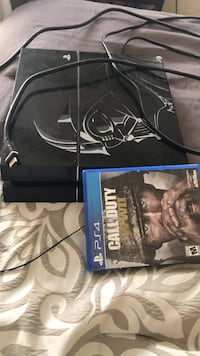 black Sony PS4 console with controller and game case 870 km