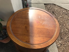 Round brown wooden table with top glass