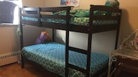 black wooden bunk bed frame and mattresses