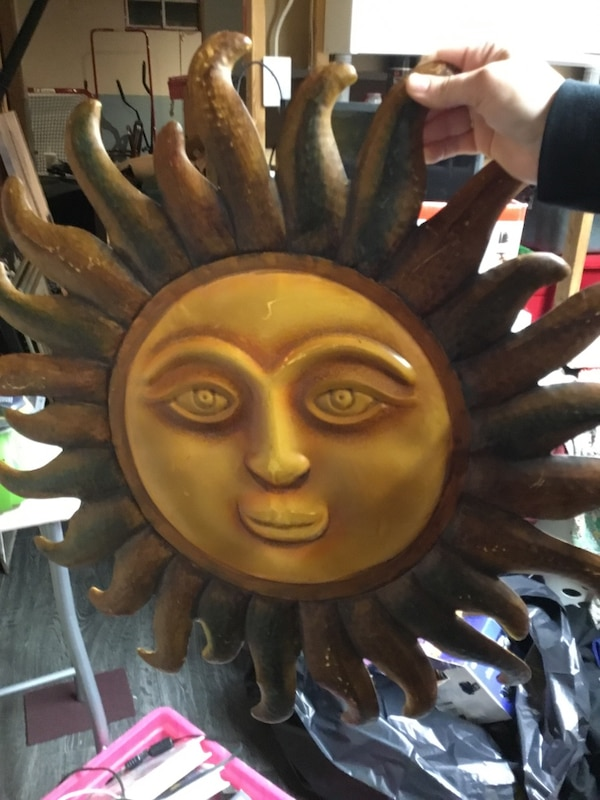 brown and yellow sun-shaped wall decor