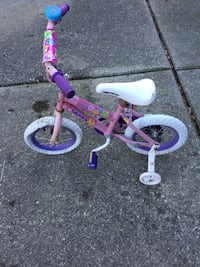 Toddler's pink and white bicycle with training wheels
