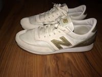 Pair of white-and-gold new balance sneakers Summerville, 29485