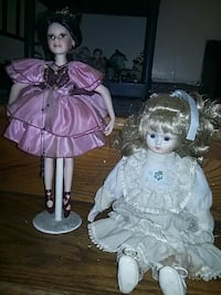 two porcelain dolls wearing purple and white dresses