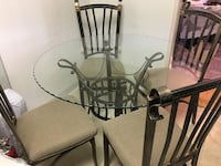round glass-top dining table with black steel frame and four chairs Alexandria, 22302