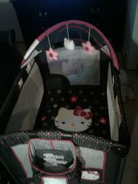 black, pink, and white Hello Kitty travel cot