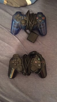 two blue and black Sony corded controllers