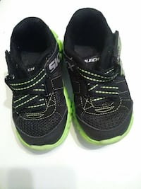 toddler's black-and-green Skechers running shoes