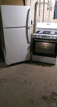 white refrigerator and white and black gas stove