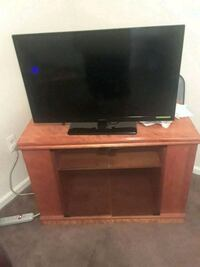 black flat screen TV with brown wooden TV stand Hackensack, 07601