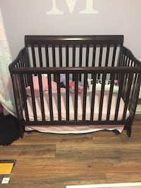 Dark brown crib with mattress