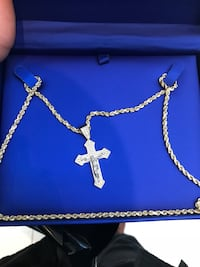 silver-colored necklace with crucifix pendant and box