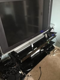 black flat screen TV with black TV stand Erie, 80516