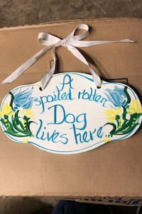 """""""A spoiled rotten Dog lives here"""" wooden sign."""