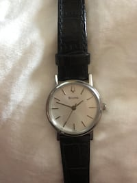 Round silver analog watch with black leather strap Whitby, L1P 1C4